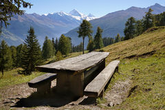 Empty rustic picnic table and benches on a slope in the mountains, Alps. Scenic landscape with empty rustic picnic table and benches made of lumber on a grassy Stock Images