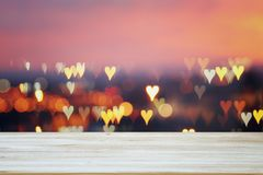 Empty rustic table in front of Valentine& x27;s day romantic glitter bokeh background with many hearts lights stock photography