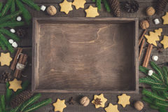 Empty rustic tray surrounded by ginger biscuits, fir branches and cones, cinnamon and walnuts. Christmas food background.  Royalty Free Stock Photo