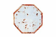 Rusty sign: empty rusty and grungy white and red old road traffic sign in octagon shape weathered under the elements Stock Images