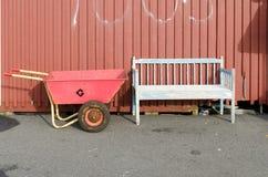 Empty rusty weelbarrow between the bench Stock Image