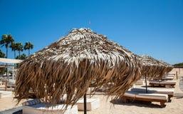 Empty sandy beach and beach beds Stock Photos