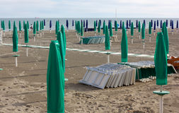 Empty Sandy Beach. With closed green and blue umbrellas Royalty Free Stock Photography