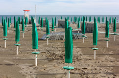 Empty Sandy Beach. With closed green umbrellas and a lifeguard watchtower Stock Images