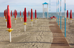 Empty Sandy Beach. With closed red umbrellas, a boardwalk and a lifeguard watchtower Royalty Free Stock Photos