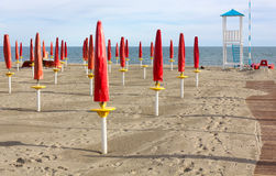 Empty Sandy Beach. With closed red umbrellas, a boardwalk and a lifeguard watchtower Royalty Free Stock Image