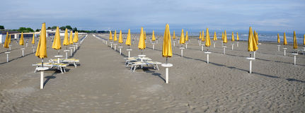 empty sandy beach with closed yellow sun umbrellas Stock Images