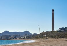 Empty sandy beach. Mediterranean Sea bay blue clear sky and chimney of cement factory in Carboneras. Province of Almeria. Spain royalty free stock photography