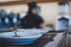 Empty saucers with spoons in the foreground of a cafe with bokeh coffee machine in the background. stock photography