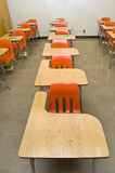 Empty School Desks. An empty class room with no students sitting in the desks. There are some notebooks laying around the room (none contain any logos stock image