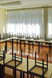 Empty schoolroom. Schoolroom interior with chairs upside-down Royalty Free Stock Photo