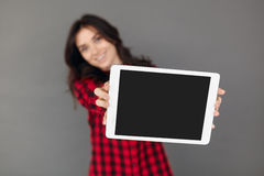 Empty screen digital tablet computer. Shallow depth of field. Empty screen digital tablet computer  on grey background. Girl holding tablet with black display Royalty Free Stock Photos