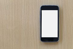 Empty Screen of Smartphone placed on a brown wooden floor. Empty Screen of Smartphone placed on a brown wooden floor and have copy space to input ideas of your Stock Image
