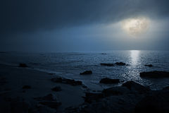 Empty seaside in a cloudy full moon night Stock Photos
