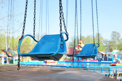 Empty seat of old carousel with chains Royalty Free Stock Photo
