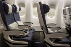 Empty seat rows on the plane. Airplane without a passenger. The board of a flying aircraft with empty chairs and covered windows Royalty Free Stock Photos