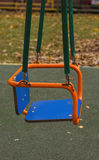 Empty seat of a swing in the yard. Empty swing in the yard against a grass Stock Images