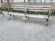 Wooden park bench double seat. Empty seating in public open city park. Wood and iron. Nobody seated. Copy space in gray paving stones in front of bench stock photography