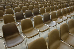 Empty seats. Endless rows of empty brown plastic seats in an exhibition hall Stock Image
