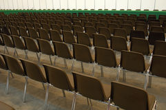 Empty seats. Endless rows of empty brown plastic seats in an exhibition hall, facing a green baize-covered table at the front Royalty Free Stock Image