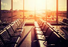 Empty seats in an airport departure hall at sunset. Empty seats in an airport departure hall at sunset, color toned picture, travel and transportation concept Royalty Free Stock Photography