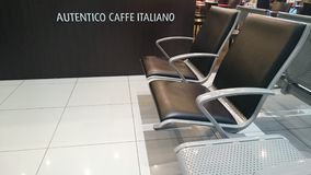 Empty seats at airport terminal with coffee invite Royalty Free Stock Photos