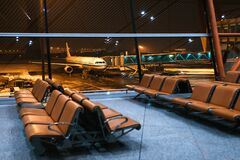 Empty seats at airport. View of the plane through the airport glass