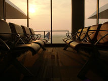 Empty seats in airport waiting lounge with airport and aircraft in background under soft sun light. View of international airport indoor hall with glass window Stock Photos