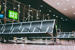 Empty seats bench in the airport hall near departure gate at international airport. Waiting for boarding at night.  stock images
