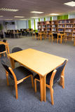 Empty seats and bookshelves at college library Royalty Free Stock Photos