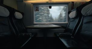 Empty seats in moving express train. Four empty seats and a table in the first class carriage of moving express train. Winter countryside scene in the window stock video