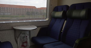 Empty seats in moving train. Empty comfortable seats and small table in the train moving through the city stock footage