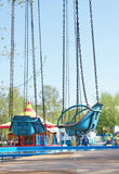 Empty seats of old carousel with chains Stock Photo