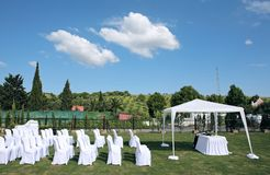 Empty seats at an outdoor wedding. Empty white seats at an outdoor wedding in the sun Royalty Free Stock Photo