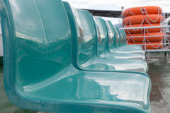 Empty seats on passenger ferry on a background of lifeboats. Royalty Free Stock Images