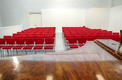 Red seats in a concert hall. Empty seats and piano in a small white concert room Royalty Free Stock Photos