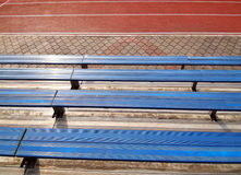 Empty seats in school stadium. A picture of some empty bleacher seating in rows, taken in a modern school sports stadium facility. With running track in stock photos