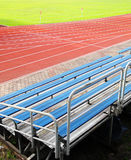 Empty seats in stadium. A picture of some empty bleacher seats in rows, taken in a modern school sports stadium facility. With running track in background and stock photos