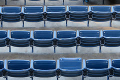 Empty seats in concrete stadium bleachers. Three rows of empty blue seats at an event stadium. Background for text or copyspace royalty free stock images