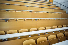 Empty seats with tables in a lecture hall Stock Photo