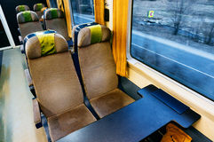 Empty seats in train car. Empty seats in train compartment with large windows Royalty Free Stock Images