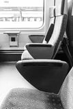 Empty seats in a train. Greyscale image of empty upholstered seats in a train in a concept of rail travel Stock Photos