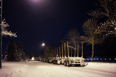 Empty semi trailers. Two eighteen wheel trucks with attached empty log trailers parked along the edge of a street under street lights at night in winter Royalty Free Stock Photo