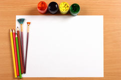 Empty sheet with paint and pencils on desk, art concept royalty free stock photos