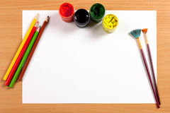 Empty sheet with paint and pencils on desk, art concept Stock Photos
