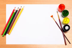 Empty sheet with paint and pencils on desk, art concept Royalty Free Stock Images