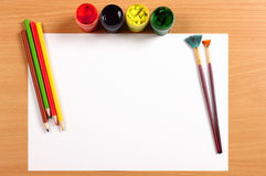 Empty sheet with paint and pencils on desk, creativity concept Royalty Free Stock Image