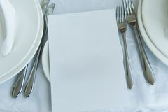 Empty sheet of paper on plate next to cutlery