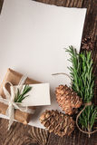 Empty sheet of paper with rosemary , cones and present vertical Stock Photo