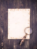 Empty sheet of paper and a vintage magnifying glass Royalty Free Stock Image